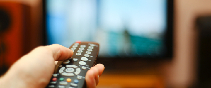 A TV remote control pointed at a blurred television set